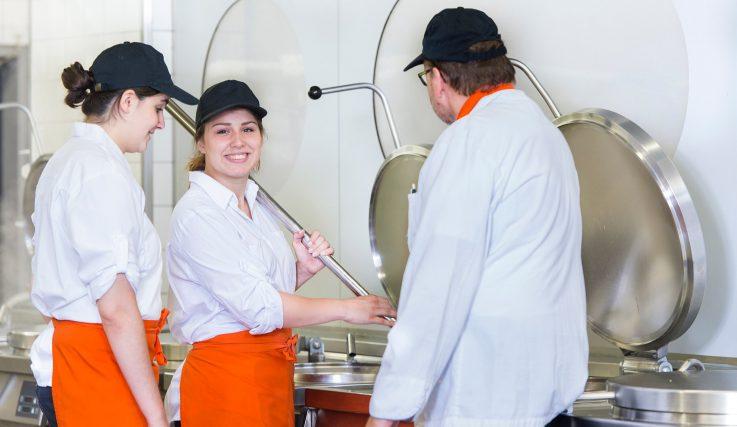 Auszubildende in der Küche am Kessel
